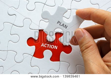 Hand Holding Piece Of Jigsaw Puzzle With Word Plan Action.