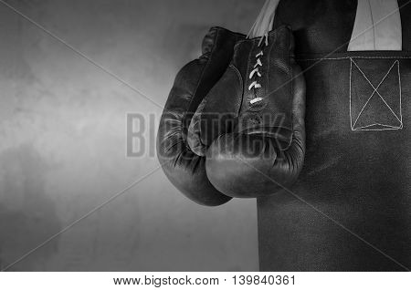 Hanging boxing gloves on a punching bag against a wall