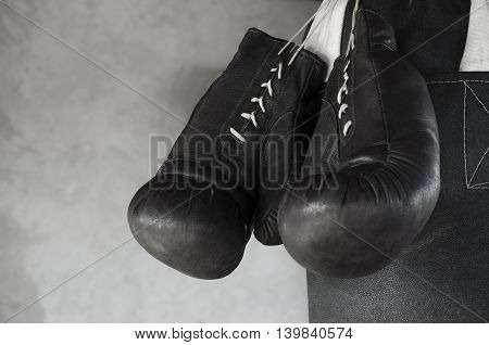 Hanging boxing leather gloves on a punching boxing bag