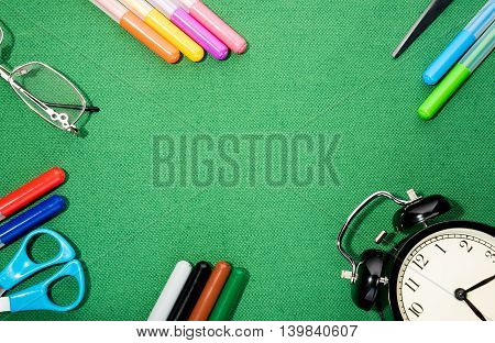 School supplies on green background ready for your design