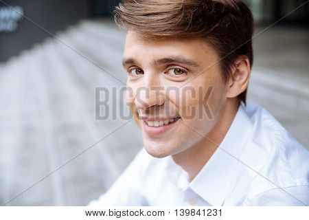 Closeup of smiling young businessman in white shirt sitting outdoors