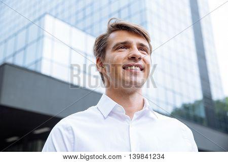 Cheerful successful young businessman standing near modern skyscraper