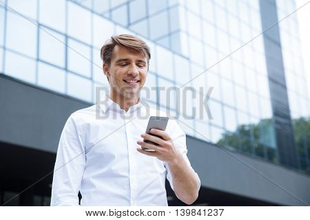 Smiling young businessman standing and using mobile phone near business center