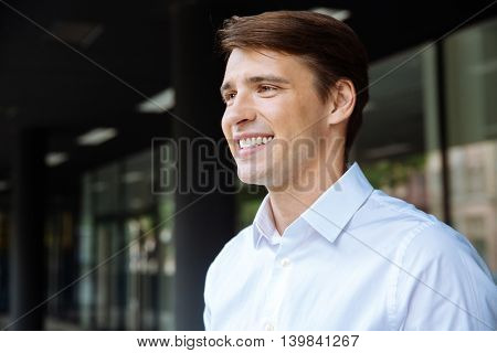 Closeup of smiling handsome young businessman standing near business center