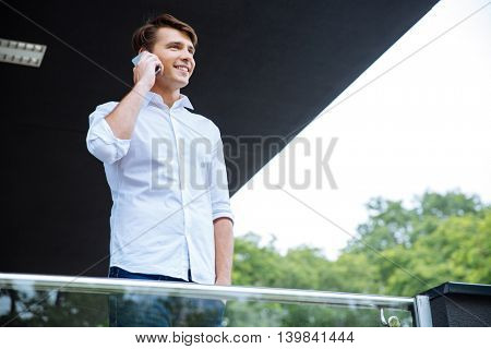 Cheerful handsome young businessman smiling and talking on cell phone on the balcony