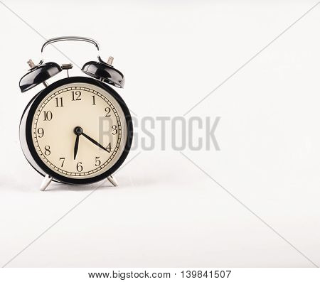 Black alarm clock on white textile background