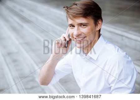 Cheerful young businessman sitting outdoors and talking on mobile phone