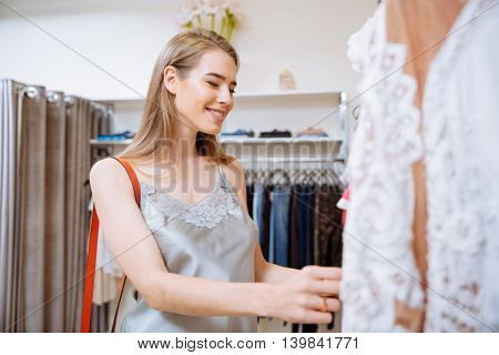 Cheerful young woman doing shopping and choosing clothes in clothing store