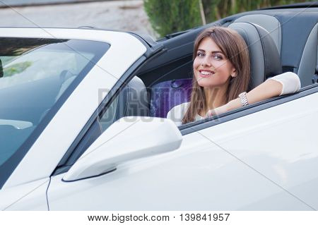 the girl sitting behind the wheel of a white sports convertible