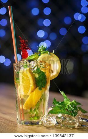 Lemonade in glass with fresh lemon on wooden table