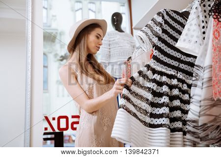 Thoughtful cute young woman in hat doing shopping in clothes shop