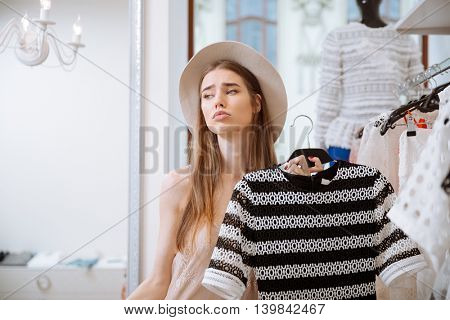 Sad pretty young woman in hat doing shopping in clothing store