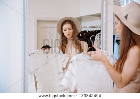 Pretty unhappy young woman looking at the mirror and choosing dress in clothing shop
