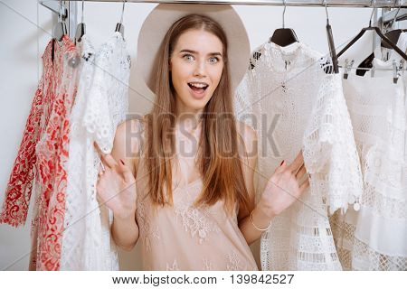 Cheerful excited young woman in hat choosing dress in clothing store