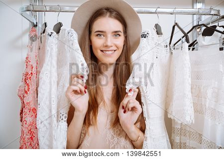Happy pretty young woman in hat choosing clothes in clothing store