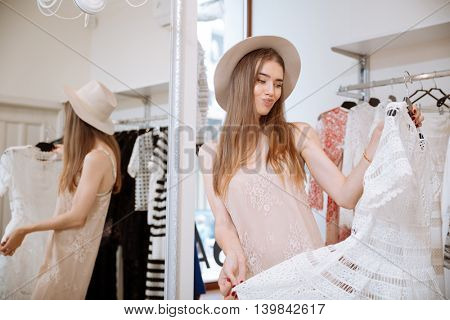 Frowning disappointed young woman in hat doing shopping and choosing dress in clothing store