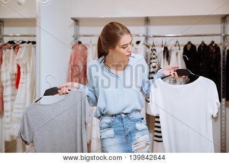 Confused pensive young woman choosing between two t-shirts in clothes shop