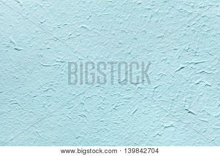 Decorative light soft blue color paper imitates the old plaster or vintage azure surface of the facade. Cerulean painted rough wall.