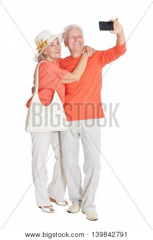 Portrait of a happy senior couple doing selfie at white background