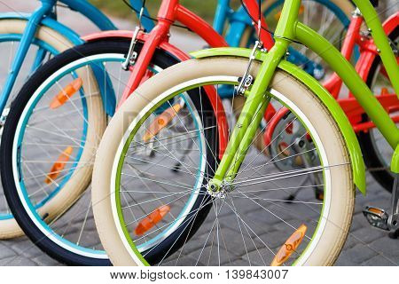 Closeup of three bright colored city urban woman bikes tires row outdoors in the park. Bright lady bicycles