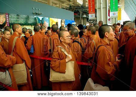 Hong Kong China - December 12 2006: Buddhist monks in orange robes carrying large shoulder bags queue to board the Ngong Ping Skyrail cable car ride to Lantau Island