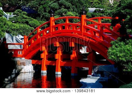 Hong Kong - January 1 2008: Classic bright orange Chinese wooden bridge spans a lagoon in the Nan Lian Garden