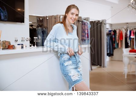 Portrait of smiling attractive young woman shop assistant stading in clothing store