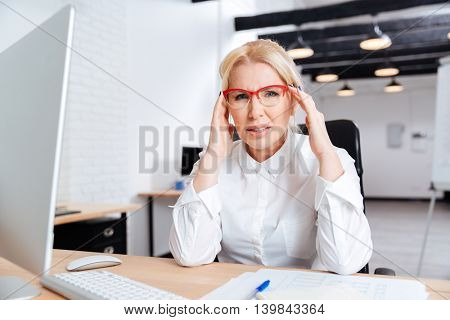 Mature businesswoman sitting at her workplace and thinking about work in office
