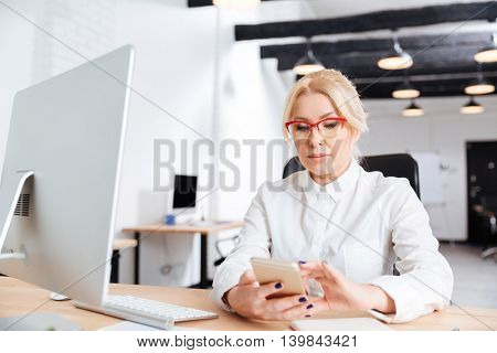 Beautiful mature woman using smart phone in the office
