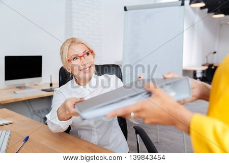 Two businesswomen working in the office with folders