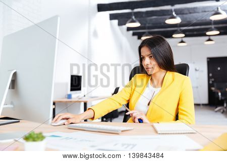 Portrait of a serious young businesswoman using laptop in office