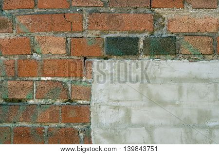Old brick wall with cracks partly covered with plaster