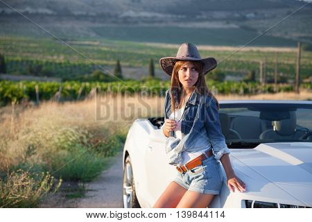 Cowboy girl standing next to a white cabriolet