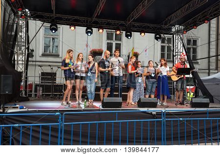 CRACOW POLAND - JULY 24 2016: Pilgrims of World Youth Day sing and dance on the St. Maria Magdalena Square in Cracow. Poland