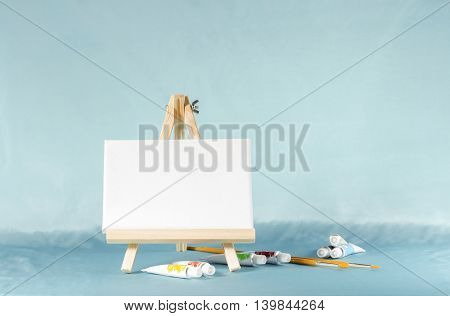 Small easel with a blank canvas on a blue background with watercolors