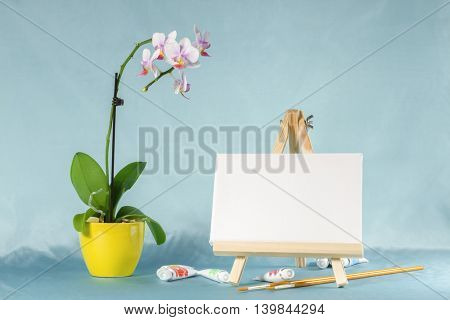 Still life with easel with a blank canvas, watercolor and  orchid flower