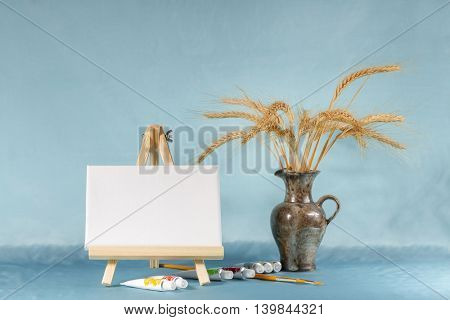 Still life with easel with a blank canvas, watercolor and wheat ears