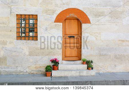 Old Wooden Door on Grunge sandstone Wall. Temple.