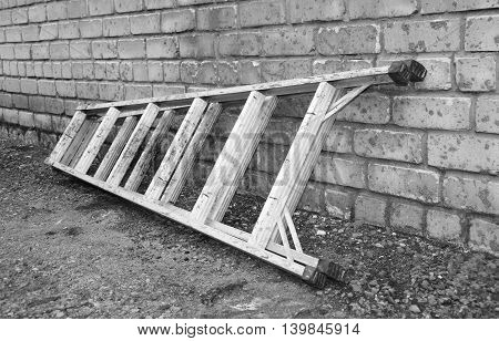Old ladder against a brick wall white black