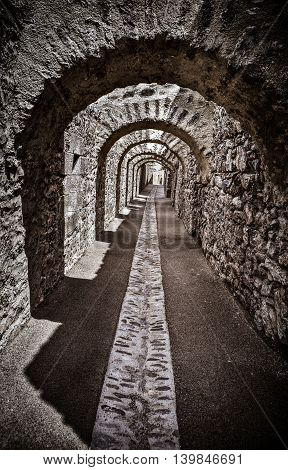 Long passage under stone arches from the old town of Villefranche de Conflent in the Conflent region of Catalonia, Pyrenees-Orientales department, France