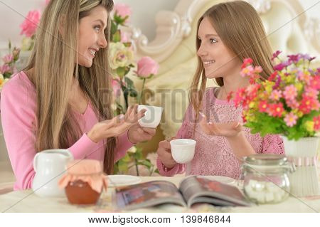 Smiling mother with  daughter drinking  tea with magazine at kitchen