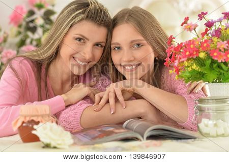Smiling mother with  daughter  with magazine at kitchen