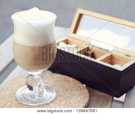 Cappuccino in a glass mug with a wooden box for sugar on table