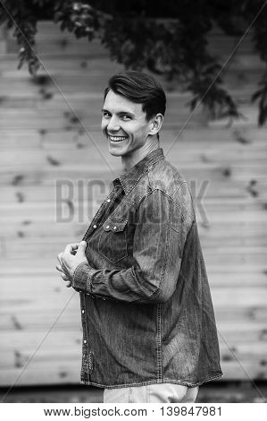 young handsome man in a denim shirt posing against a background of a wooden wall