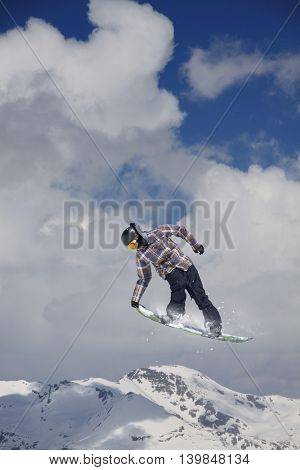 Snowboarder jumps high in the mountains.