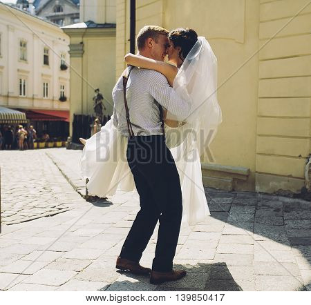 groom carries his bride in his arms through the old town