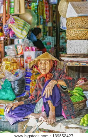 Asian Blind Old Woman Selling Bunches Of Bananas In Market