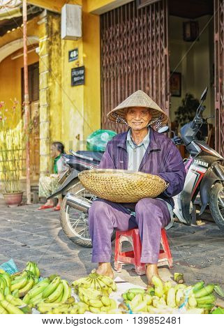 Asian Man Selling Bunches Of Bananas In The Street Market