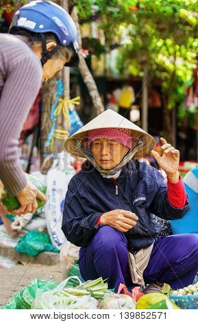 Asian Trader In The Traditional Vietnamese Hat Selling Fresh Vegetables