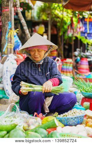 Asian Trader Selling Sprouting Onion And Other Fresh Vegetables